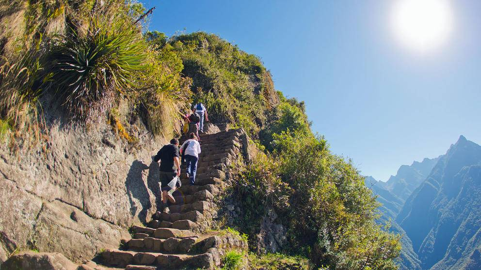 Visitors hiking up a stairway on the Inca trail at Machu Picchu, Peru